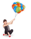 Junge Frau, die bunte Ballone anhält Stockfoto