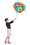 Junge Frau, die bunte Ballone anhält Stockbild