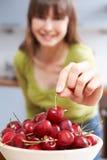 Junge Frau, die Cherry From Wooden Bowl nimmt Stockbild