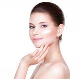 Junge Frau, die Creme auf ihrem hübschen Gesicht aufträgt lizenzfreie stockfotografie