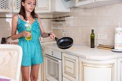Junge Frau, die das Öl auf einer Bratpfanne verbreitet Lizenzfreie Stockfotos