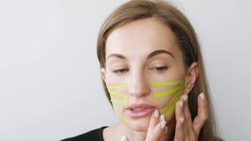 Junge Frau, die das Aufnehmen des Gesichtes für Verjüngung tut stock video