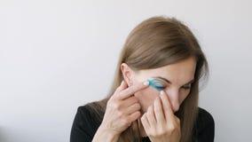 Junge Frau, die das Aufnehmen um die Augen zu verjüngen tut stock footage