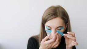 Junge Frau, die das Aufnehmen um die Augen zu verjüngen tut stock video footage
