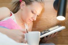Junge Frau, die in das Bett liest eine Zeitschrift legt Lizenzfreies Stockfoto