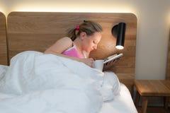 Junge Frau, die in das Bett liest eine Zeitschrift legt Lizenzfreie Stockfotos