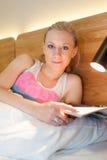 Junge Frau, die in das Bett liest eine Zeitschrift legt Stockbild