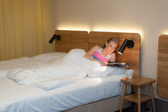 Junge Frau, die in das Bett liest eine Zeitschrift legt Lizenzfreies Stockbild