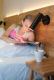 Junge Frau, die in das Bett liest eine Zeitschrift legt Stockfotografie