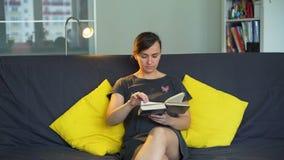 Junge Frau, die das Buch in ihrem Appartement liest stock footage