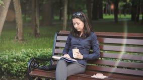 Junge Frau, die das Buch im Allgemeinen Park liest stock footage
