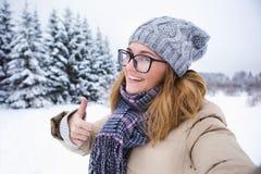 Junge Frau, die das Foto auf einem Hintergrund des schneebedeckten Winterwaldes macht Lizenzfreies Stockfoto