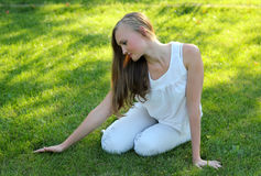 Junge Frau, die das Gras streicht Stockfotos