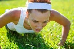 Junge Frau, die das Handeln drückt, ups auf Grün Stockfoto