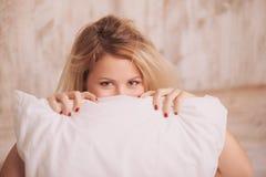 Junge Frau, die das Kissen umarmt Lizenzfreie Stockbilder