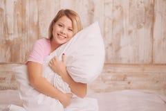 Junge Frau, die das Kissen umarmt Stockfoto