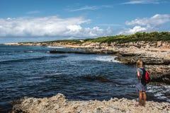 Junge Frau, die das Meer betrachtet Stockfoto