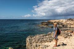 Junge Frau, die das Meer betrachtet Stockfotografie