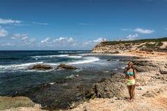 Junge Frau, die das Meer betrachtet Stockfotos