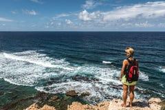 Junge Frau, die das Meer betrachtet Stockbilder