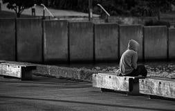 Junge Frau, die in das Meer mit leerer Bahn sitzt und anstarrt Lizenzfreie Stockfotos