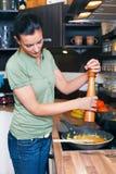 Junge Frau, die das Mittagessen vorbereitet Lizenzfreies Stockbild