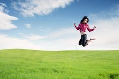 Junge Frau, die das neue Jahr springt auf Feld genießt lizenzfreie stockfotografie