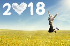 Junge Frau, die das neue Jahr springt auf Feld genießt lizenzfreies stockbild