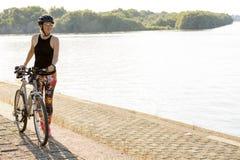 Junge Frau, die das Radfahren nahe dem Fluss genießt Lizenzfreie Stockbilder