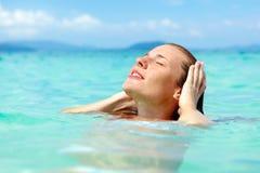 Junge Frau, die das Schwimmen in erneuernmeerwasser genießt lizenzfreies stockfoto