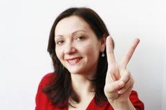 Junge Frau, die das Symbol des Friedens zeigt Lizenzfreies Stockbild