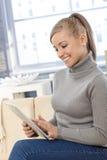 Junge Frau, die das Tablettelächeln verwendet Lizenzfreie Stockfotografie