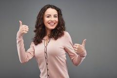 Junge Frau, die Daumen lächelt und sich zeigt lizenzfreies stockbild