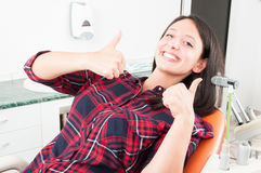 Junge Frau, die Daumen oben im Zahnarztstuhl zeigt Lizenzfreies Stockbild