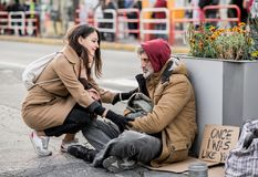Junge Frau, die dem obdachlosen Bettlermann Geld sitzt in der Stadt gibt lizenzfreie stockfotos