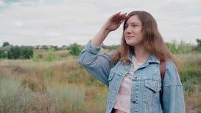 Junge Frau, die den Abstand vor dem hintergrund der Natur untersucht Nette lächelnde weibliche Stellung draußen stock footage