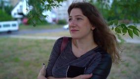 Junge Frau, die den Abstand vor dem hintergrund der Natur untersucht Nette lächelnde weibliche Stellung draußen stock video footage