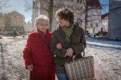 Junge Frau, die den Einkauf mit älterer Frau anstrebt stockbilder