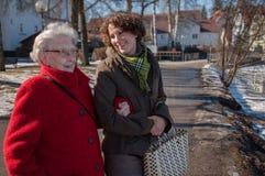 Junge Frau, die den Einkauf mit älterer Frau anstrebt lizenzfreies stockbild