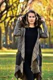 Junge Frau, die den eleganten Designmantel, werfend im Herbstpark trägt auf Stockfoto