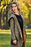 Junge Frau, die den eleganten Designmantel, werfend im Herbstpark trägt auf Lizenzfreie Stockfotos