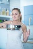 Junge Frau, die den Geruch ihres Kochens genießt Stockbilder