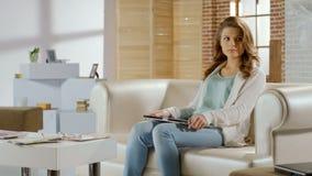 Junge Frau, die den geschlossenen Laptop, sitzend auf Couch, Umkippen mit Auseinanderbrechen der schlechten Nachrichten hält lizenzfreie stockfotos