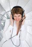 Junge Frau, die in den großen Kopfhörern schauen in der Kamera ist Stockfotografie