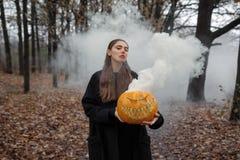 Junge Frau, die den Halloween-Kürbis mit dem weißen Rauche von innen kommt von ihm hält stockbild