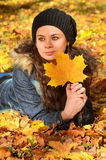 Junge Frau, die in den Herbstblättern sich entspannt Lizenzfreie Stockbilder