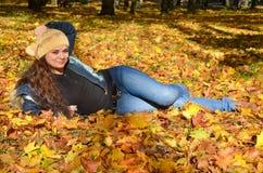 Junge Frau, die in den Herbstblättern und -c$lächeln liegt Stockbild