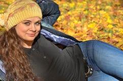 Junge Frau, die in den Herbstblättern und -c$lächeln sich entspannt Lizenzfreie Stockfotos