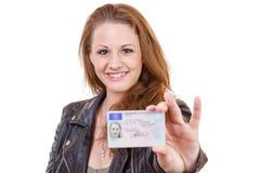 Junge Frau, die den ihren Führerschein zeigt Lizenzfreie Stockfotos