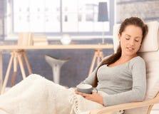 Junge Frau, die in den Lehnsesselaugen geschlossen sich entspannt Stockfotos
